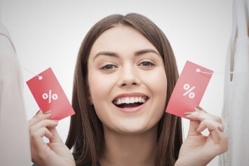 clothing, fashion, sale, shopping and people concept - happy woman showing discount tags with percent on clothes at home wardrobe or shop